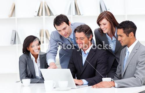 Multicultural business team looking at a laptop