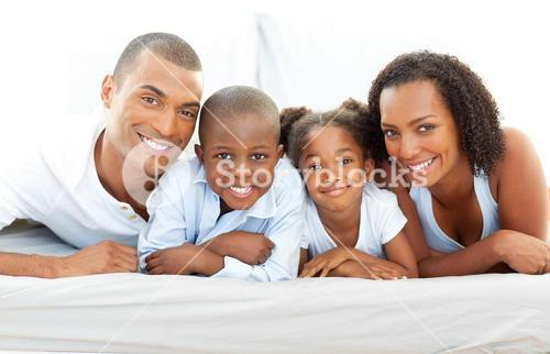 Happy family having fun lying down on bed