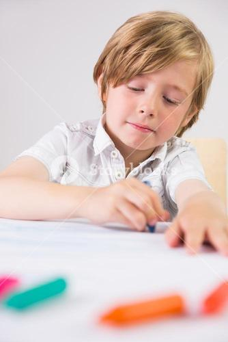 Student using crayons to draw