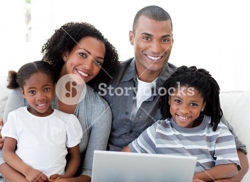 Happy family using a laptop in the livingroom