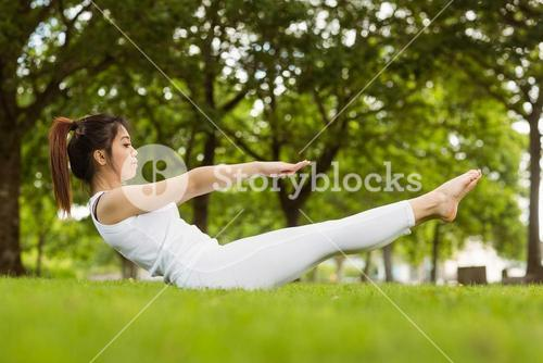 Side view of doing the boat pose in park