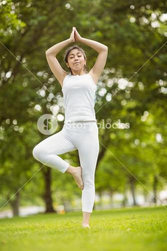 Fit woman standing in tree pose in park