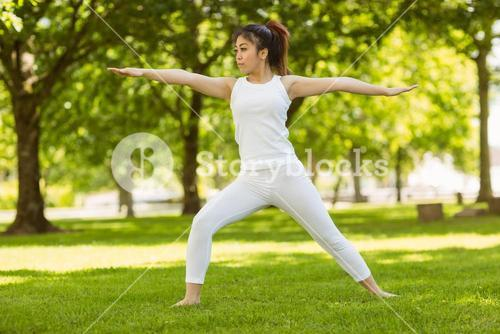 Toned woman doing stretching exercises in park