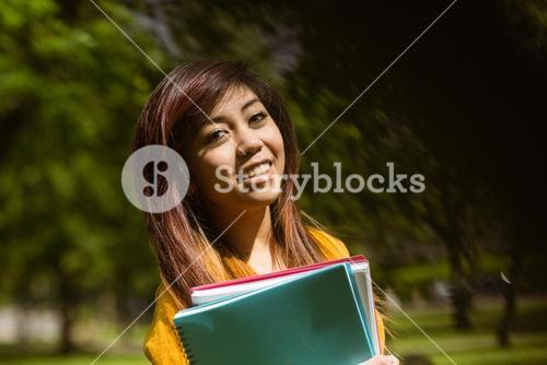 Female college student with books in park