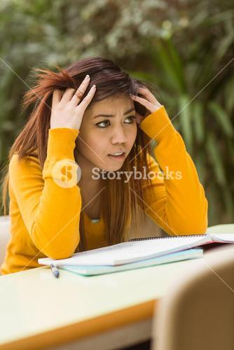 Frustrated female college student doing homework