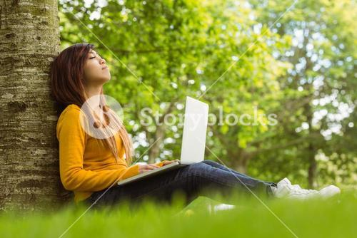 Relaxed woman using laptop in park