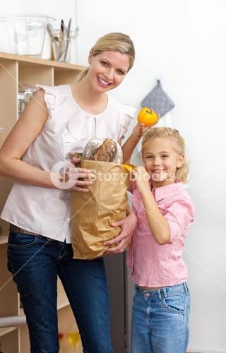 Happy mother and her Little girl unpacking grocery bag
