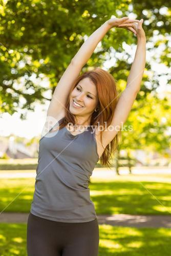 Pretty redhead stretching in the park
