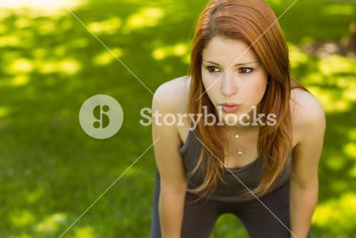 Pretty redhead panting in the park