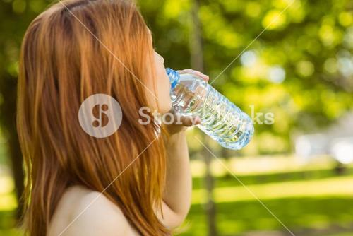 Pretty redhead drinking water in park
