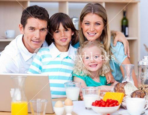 Joyful family using laptop during the breakfast