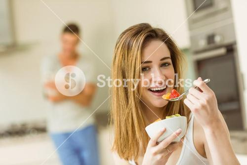 Woman eating fruit salad at breakfast