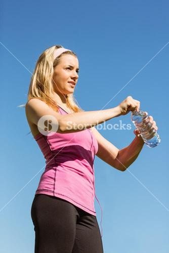 Fit blonde opening her water bottle