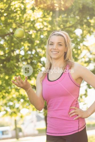 Fit blonde tossing green apple