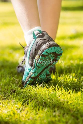 Woman in running shoes stepping on grass