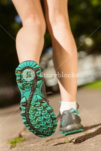 Woman in running shoes stepping on path