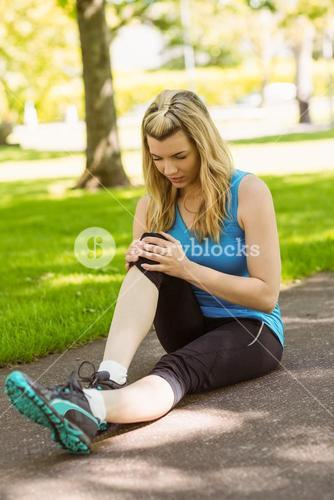 Fit blonde touching her injured knee on path