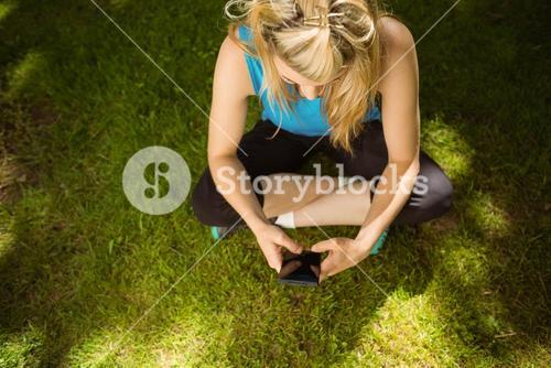 Fit blonde texting on her smartphone