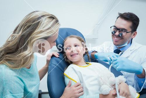 Dentist examining girls teeth with assistant