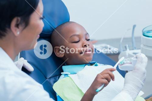 Female dentist teaching boy how to brush teeth