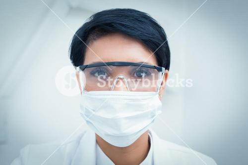 Dentist wearing surgical mask and safety glasses