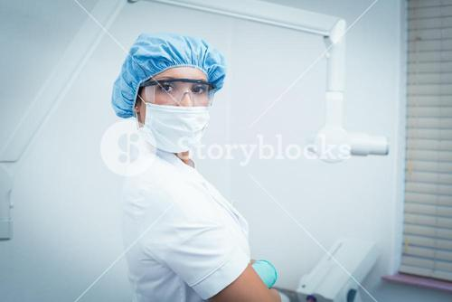 Female dentist wearing surgical mask and safety glasses