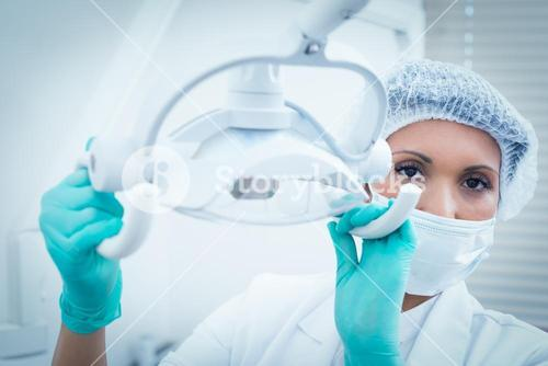 Female dentist in surgical mask adjusting light