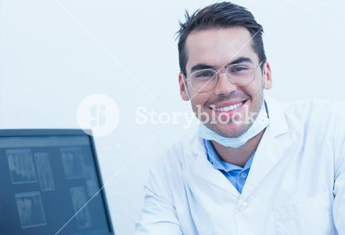 Smiling male dentist with computer monitor