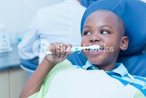 Boy brushing teeth in the dentists chair