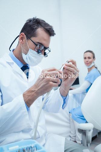 Concentrated dentist looking at dental tool