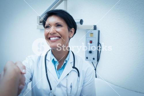 Cheerful dentist shaking hands with patient
