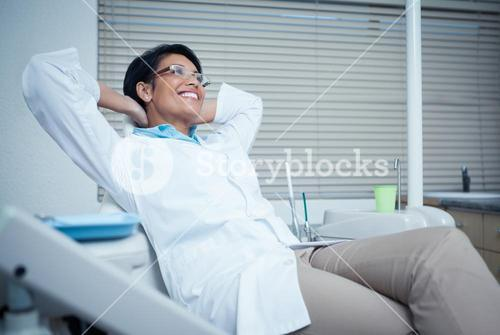 Relaxed smiling female dentist sitting on chair