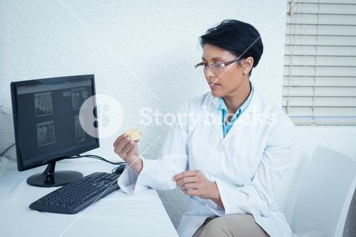 Dentist holding mouth model besides computer