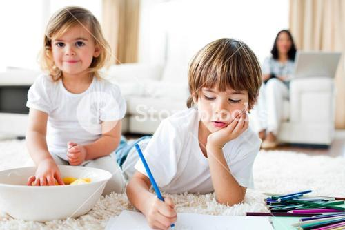 Serious little boy drawing and his sister eating chips