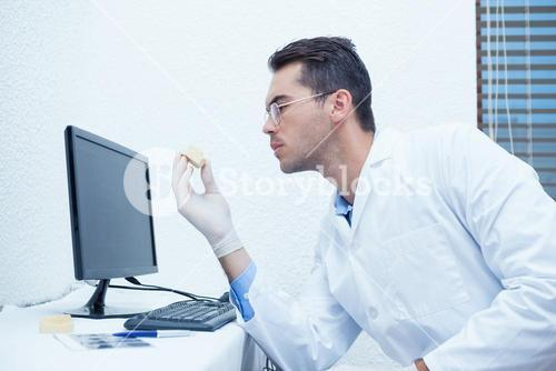 Dentist holding mouth model by computer