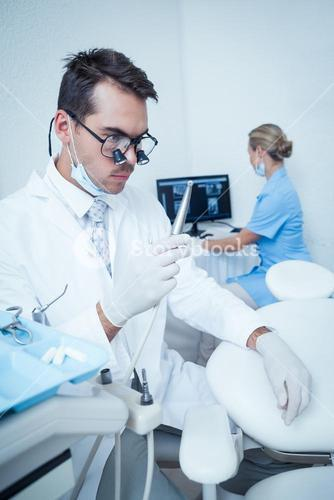 Dentist looking at dental drill