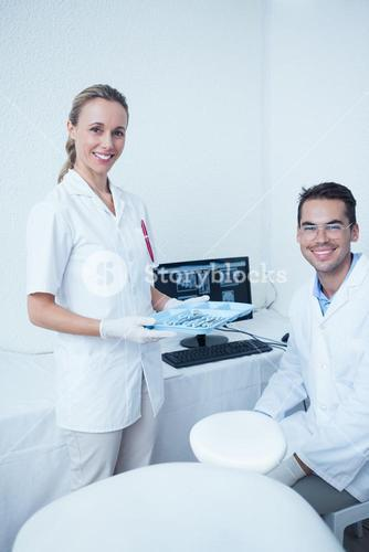 Portrait of smiling dentists with computer monitor