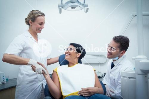 Male dentist with assistant shaking hands with woman