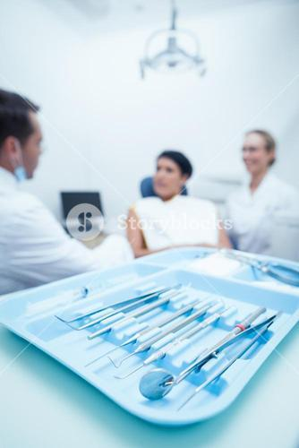 Dentist and assistant with female patient