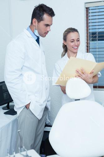 Smiling dentists discussing reports