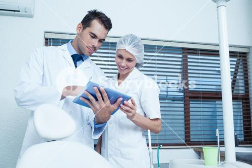 Dentists using digital tablet