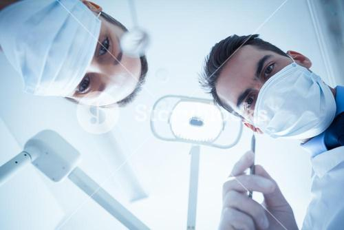 Dentists in surgical masks holding dental tools