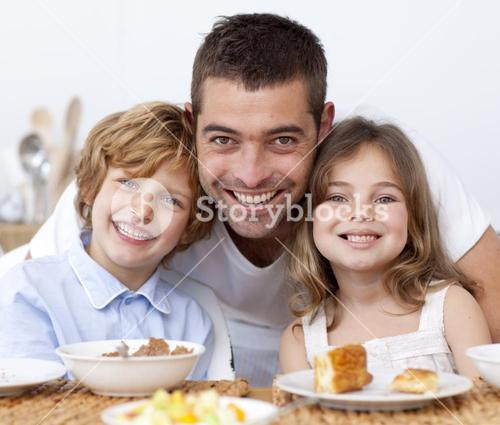 Portrait of children having breakfast with their father
