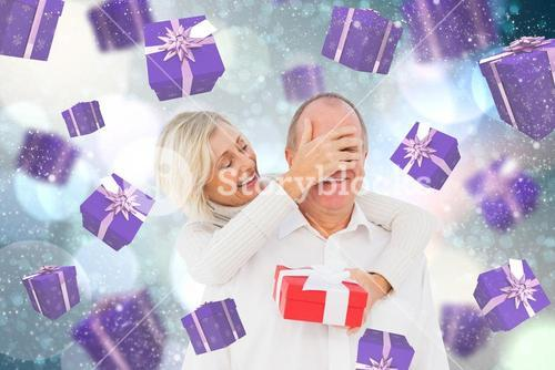 Composite image of woman surprising man with gift