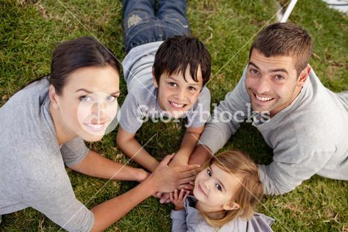 young Parents and kid lying on garden with hands together
