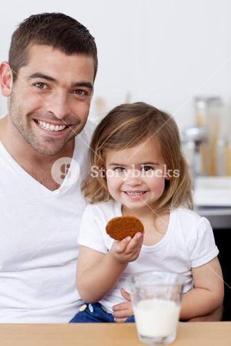 Father and daughter eating biscuits with milk
