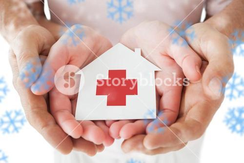 Composite image of couple holding paper house with red cross in hands