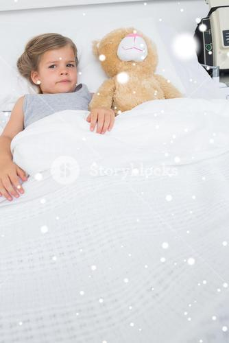 Composite image of girl with teddy bear lying in hospital bed