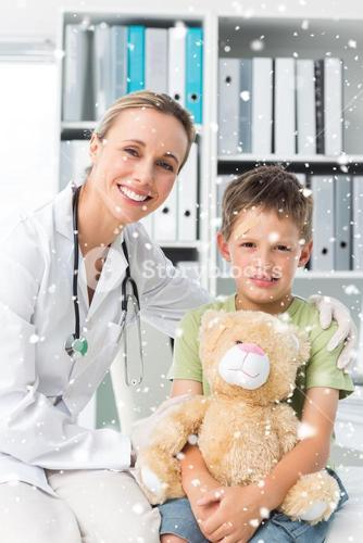 Composite image of friendly doctor with boy holding teddy bear