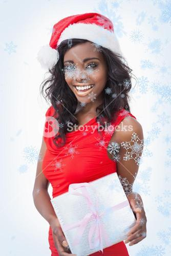 Composite image of woman standing holding a gift while smiling